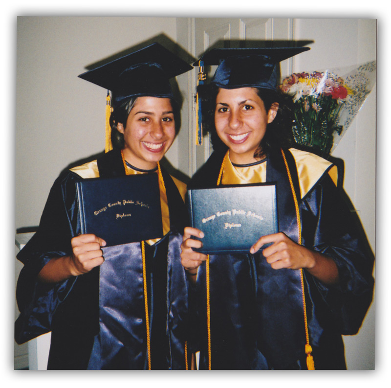Ida and Anna Eskamani in high school graduation gowns holding diplomas